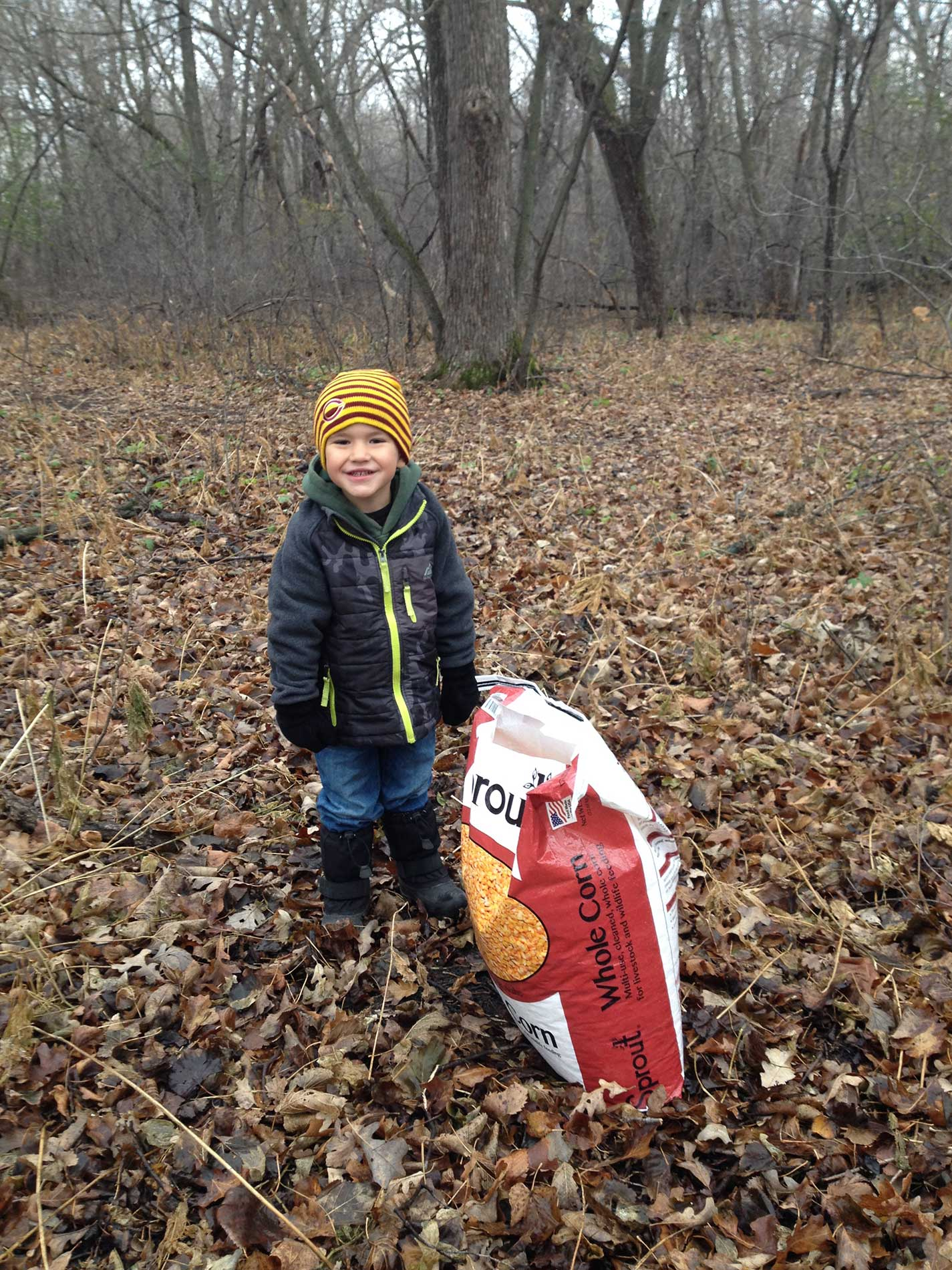 Reese helping me put corn our for the deer and turkeys