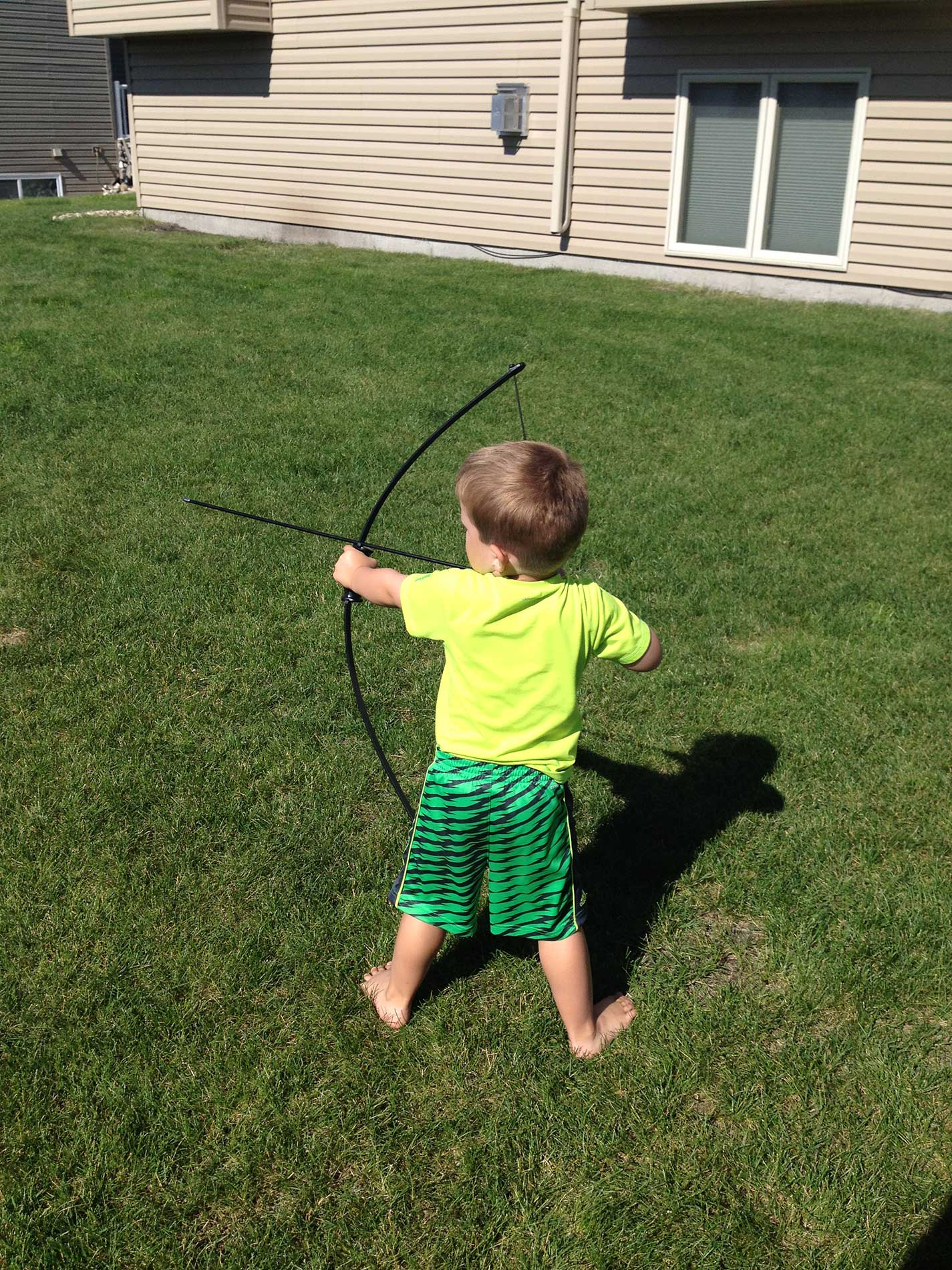Reese practicing shooting his bow in the backyard at the age of three.